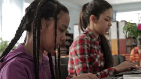 Two sisters with long hair in school library. Two girls with long hair working in the school library. They are sisters. Use the computer stock video footage