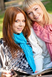 Two sisters looking at camera in the park Royalty Free Stock Photography