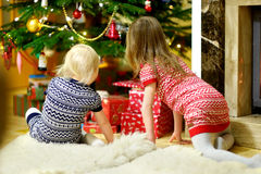Two sisters looking for gifts under a tree Stock Photo