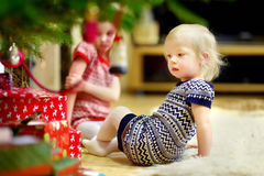 Two sisters looking for gifts under a tree Royalty Free Stock Photo