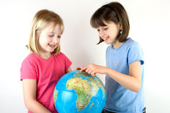 Two Sisters Looking at a Globe Stock Photo