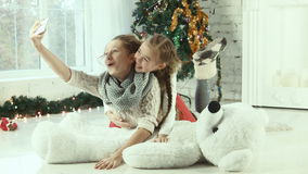 Two sisters looking at a smartphone and laughing. Two friendly sisters looking at a smartphone and laughing on the background of Christmas tree stock footage