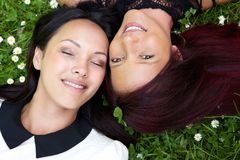 Two sisters lying on grass and smiling Royalty Free Stock Images