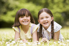Two sisters lying outdoors smiling Stock Photography