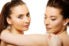 Two sisters with make up embracing. Stock Photos