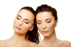 Two sisters with make up and eyes closed. Stock Image