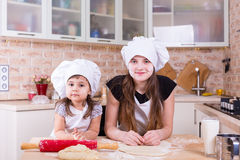 Two sisters making dough at home Royalty Free Stock Photography