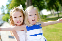 Two sisters making funny faces outdoors. Two little sisters making funny faces outdoors Stock Images