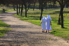 Two sisters (nuns) walking in a park along the path. Stock Photo