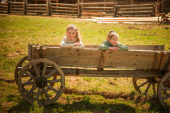 Two sisters on old wooden wagon Stock Photography