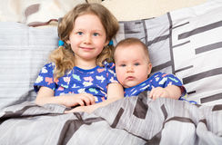 Two sisters. Older sister kid hugging his newborn little sister. royalty free stock photos