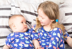 Two sisters. Older sister kid hugging his newborn little sister. royalty free stock images
