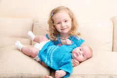 Two sisters. Older sister kid hugging his newborn little sister. stock photo