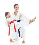 Two sisters, one teaches a sister beat kick leg Royalty Free Stock Image