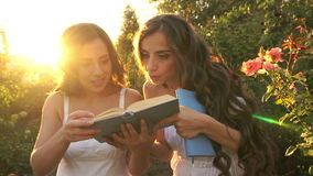 Two sisters outdoors with books. Two sisters in white dresses carefully read the book. The girl slams the book. Family time stock footage