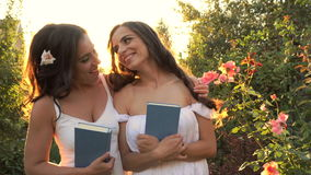 Two sisters outdoors with books. Two sisters in white dresses embrace. Girls hold books in their hands. Family time stock video footage