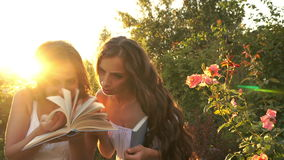 Two sisters outdoors with books. Two sisters in white dresses are looking for the right page in the book. Education. Reading books. Family time stock footage