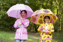 Two sisters outdoors in rain with umbrellas royalty free stock photography