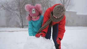 Two sisters outdoors in the winter make a snowman. Older and younger sisters with fun make a snowman in the street stock video