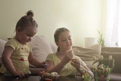 Kids Easter preparation by painting Easter eggs royalty free stock photography