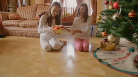 Two sisters in pajamas running in living room to open their Christmas gifts. Two sisters in pajamas running in living room to open Christmas gifts stock video footage