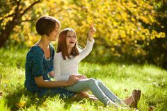 Two sisters in a park in autumn Stock Image