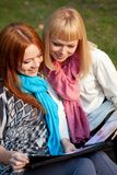 Two sisters with photo album in the park Stock Photography