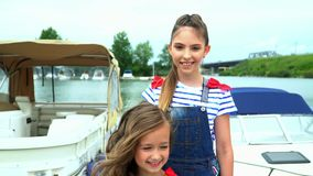 Two sisters are photographed on the yacht. Two sisters embrace each other on a pier at water. On this video you can see as the little girl the blonde rotates stock video footage