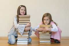 Two sisters with a pile of books on the floor in the room. The concept of education and development of children. Love of royalty free stock photo