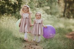 Two sisters are playing balloons. kids playing together. Happy sister with balloons walking on the spring field royalty free stock photography