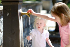 Two sisters playing with drinking water fountain Stock Photography