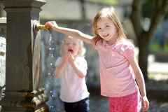 Two sisters playing with drinking water fountain Royalty Free Stock Images