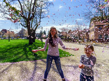 Two sisters playing with falling petals on the sun Royalty Free Stock Image