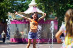 Two sisters playing with fountain splash Royalty Free Stock Image
