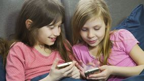 Two sisters playing in gadgets in bed at home. Dressed in pink pyjamas with a cellphone or smartphone. female kids is relaxing stock video footage