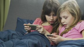 Two sisters playing in gadgets in bed at home. Dressed in pink pyjamas with a cellphone or smartphone. female kids is relaxing stock video