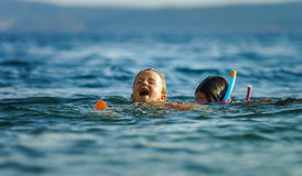 Two sisters playing games and swimming in the sea Stock Images