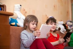 Girls playing tablets. Two sisters playing games on tablets in children`s room stock photos