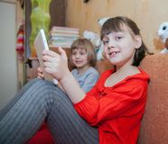 Sisters playing games on tablets Royalty Free Stock Photo