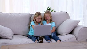 Two sisters playing with laptop. On sofa stock footage
