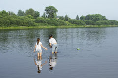 Two sisters playing with paper boats by a river Stock Photos