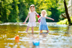 Two sisters playing with paper boats by a river Stock Photography