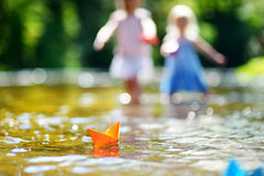 Two sisters playing with paper boats by a river Royalty Free Stock Photo