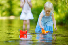 Two sisters playing with paper boats by a river Stock Image
