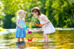 Two sisters playing with paper boats by a river Royalty Free Stock Images