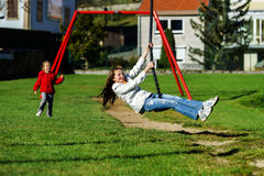 Two sisters playing in the playground, sunny day Royalty Free Stock Image