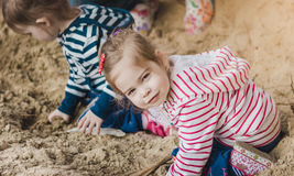 Two sisters playing on the sand in the forest Royalty Free Stock Photography