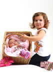 Two sisters playing and smiling in a basket Stock Photos