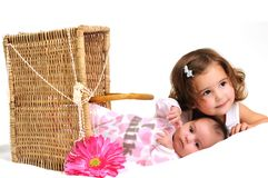 Two sisters playing and smiling in a basket Royalty Free Stock Image