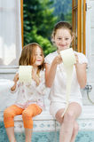 Two sisters playing with toilet paper roll Stock Photo